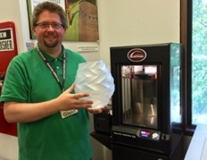 Glenn Kneebone holds 3d printed object next to the printer