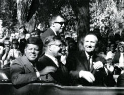Senator Mike Mansfield riding in a car with President John F. Kennedy, taken outside the Mansfield home in Great Falls, Montana. A crowd of spectators look on.