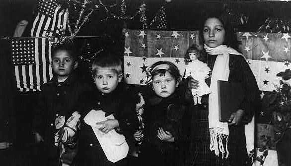 Four immigrant children at Ellis Island surrounded by gifts and the American flag.