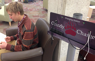 picture of student using grizzly charging station in mansfield library east faculty