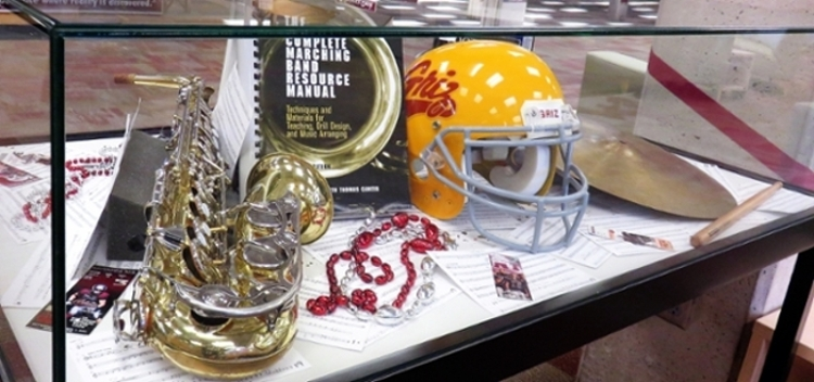 Display case at the Mansfield Library showing school song music scores, a saxophone, as well as for spirit and an older football helmet.