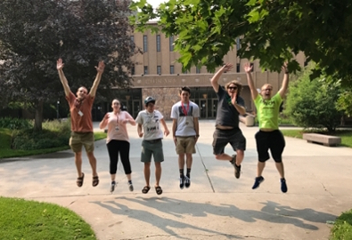 four students jumping for joy outside the front of Mansfield Library on a summer day